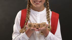 Cheerful schoolgirl holding wooden cubes with math word against blackboard. Stock footage stock footage