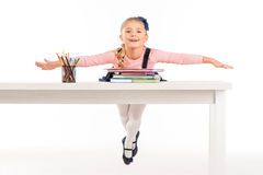Cheerful schoolgirl lying on desk. With books on white Royalty Free Stock Images