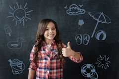 Cheerful schoolgirl putting her thumbs up and dreaming about summer. Summer holidays. Optimistic cute schoolgirl feeling glad while putting her thumbs up and stock images