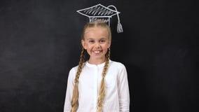 Cheerful schoolgirl smiling on camera, academic cap painted on blackboard, geek