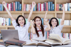 Cheerful schoolgirls raise hands together in library Stock Photos