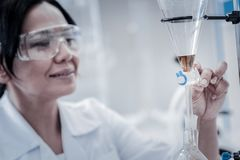 Cheerful scientist regulating lab glassware fixed on metal stand. Attentive preparation. Selective focus on a glassware containing a chemical liquid examined by stock photo
