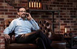 Cheerful self employed man having a phone conversation. Distance communication. Handsome delighted good looking businessman putting the smartphone to his ear and Royalty Free Stock Photography