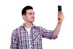 Cheerful selfie. Cheerful young man in shirt holding mobile phone and making photo of himself while standing against white isolated background Royalty Free Stock Images