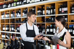 Cheerful seller man giving sample taste of wine. Cheerful seller men wearing apron giving sample taste of wine in glass to women customer in wine store Stock Photos