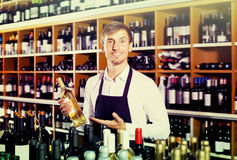 Cheerful seller man promoting bottle of wine. Cheerful seller man wearing apron promoting bottle of wine in wine store Stock Photos