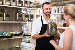 Cheerful seller in store of ecological goods. Portrait of cheerful male seller having jar with dried herbs in hands in store with ecological goods Royalty Free Stock Photos
