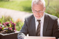 Cheerful senior businessman sitting at the table. Full of gladness. Positive smiling senior businessman sitting at the table and using laptop while expressing stock image