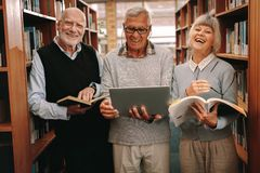 Cheerful senior colleagues standing in a library royalty free stock photo