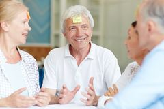 Game for fun. Cheerful senior companions describing what is written on notepapers on their foreheads Stock Images