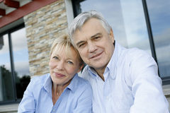 Cheerful senior couple in front of house royalty free stock images