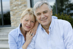 Cheerful senior couple in front of their home Royalty Free Stock Images