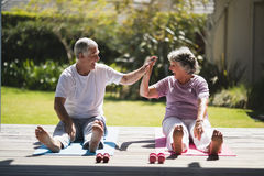 Cheerful Senior Couple Giving High Five While Exercising Together At Porch Royalty Free Stock Photos