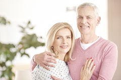 Cheerful senior couple having fun together. Shot of a happy senior couple standing at home and embraching eachother while looking at camera and smiling Stock Photography