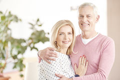 Cheerful senior couple having fun together. Shot of a happy senior couple standing at home and embraching eachother while looking at camera and smiling Royalty Free Stock Image