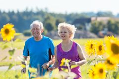 Cheerful senior couple jogging together outdoors in the countrys Royalty Free Stock Photo