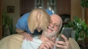 Cheerful senior couple at home. Husband using smartphone, browsing, reading. Wife comming hugging stock video