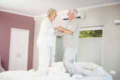 Cheerful senior couple jumping on bed royalty free stock photos