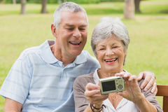 Cheerful senior couple photographing themselves at park Royalty Free Stock Photography