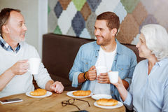 Cheerful senior couple resting with their adult grandson. Family meeting. Positive smiling aged couple and their grandson sitting at the table and having lunch Stock Photography