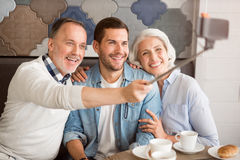 Cheerful senior couple resting with their adult grandson. Happy together. Cheerful delighted smiling senior couple sitting at the table with their adult grandson Royalty Free Stock Images