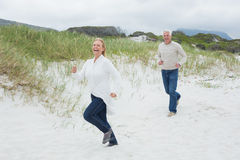 Cheerful senior couple running at beach Stock Photo