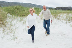 Cheerful senior couple running at beach Stock Photography