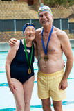Cheerful senior couple standing at poolside royalty free stock photo