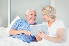 Cheerful senior couple using digital table on bed Royalty Free Stock Photography