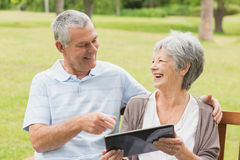 Cheerful senior couple using digital tablet on bench at park Stock Images