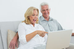 Cheerful senior couple using laptop at house Stock Photos