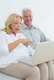 Cheerful senior couple using laptop at house Stock Photo