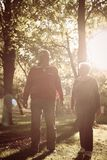 Senior couple walking together trough park and having c stock images
