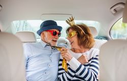 Free Cheerful Senior Couple With Party Accessories Sitting In Car, Having Fun. Stock Image - 159257091