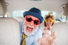 Free Cheerful Senior Couple With Party Accessories Sitting In Car, Having Fun. Stock Image - 159830871
