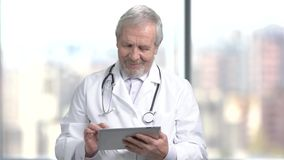 Cheerful senior doctor using digital tablet. Elderly male doctor in white coat texting a message on blurred background stock footage