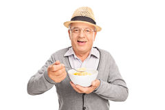 Cheerful senior eating cereal from a bowl Royalty Free Stock Photos