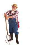 Cheerful senior farmer leaning on hay fork. Classic smiling senior farmer with straw hat, plaid shirt, bib overalls, and hay fork. Vertical layout, isolated on royalty free stock photo