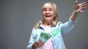 Cheerful senior female throwing euro banknotes, wasting money, loan service royalty free stock image