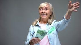 Cheerful senior female throwing euro banknotes, wasting money, loan service. Stock photo royalty free stock image