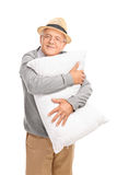 Cheerful senior gentleman hugging a pillow Royalty Free Stock Photos