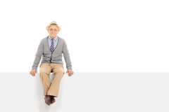 Cheerful senior gentleman sitting on a blank panel Stock Photos