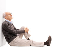 Cheerful senior gentleman sitting on the floor. And leaning against a wall isolated on white background Royalty Free Stock Images