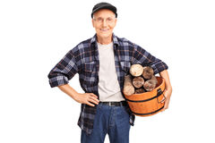 Cheerful senior holding a basket full of logs Stock Photos