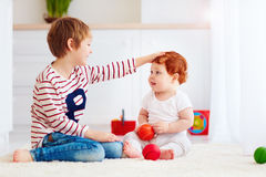 Cheerful senior kid playing with his junior toddler brother at home. Cheerful senior kid playing with his junior toddler brother on carpet at home Stock Photography
