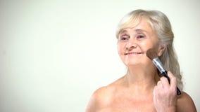 Cheerful senior lady applying powder, positive attitude to age, beauty care royalty free stock image