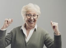 Cheerful senior lady celebrating her victory with raised fists royalty free stock images