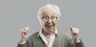 Cheerful senior lady celebrating her victory with raised fists stock photos