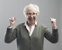 Cheerful senior lady celebrating her victory with raised fists royalty free stock photos
