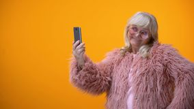 Cheerful senior lady in funny pink coat taking selfie on smartphone, having fun